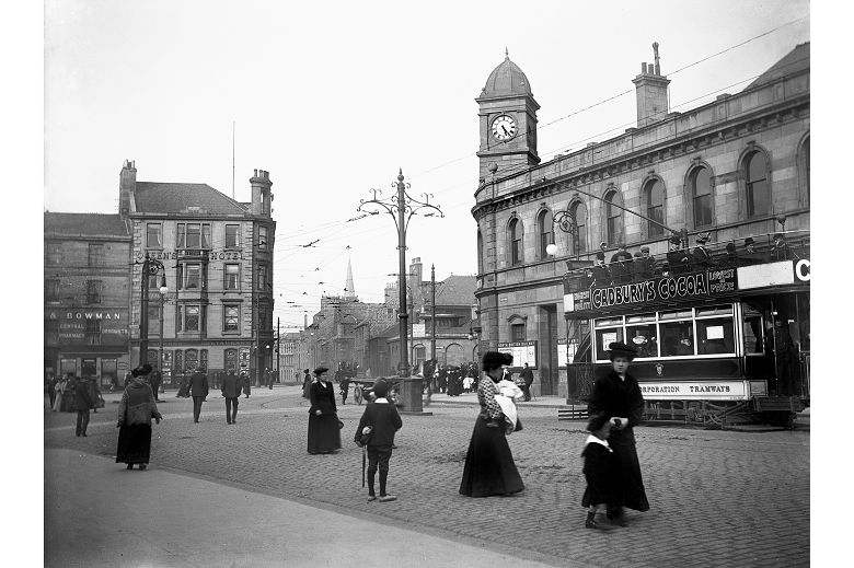 An archive photo of adult and child pedestrians, along with a tram, at a road junction