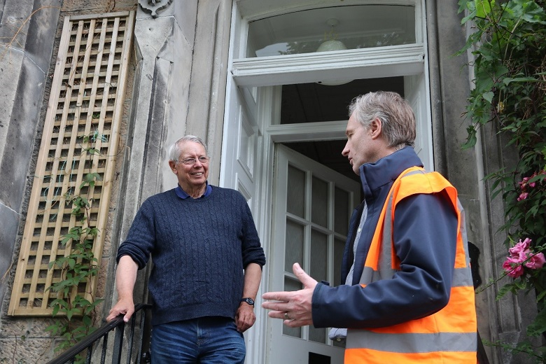 A person in high vis vest speaking to a homeowner