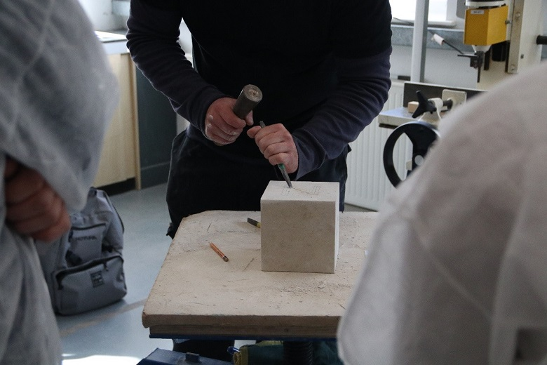 A person carving into a square block of stone