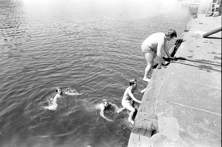 Men clambering out of water onto a jetty