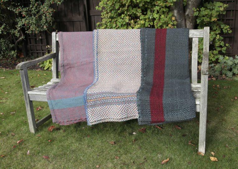 three blankets draped over a garden bench