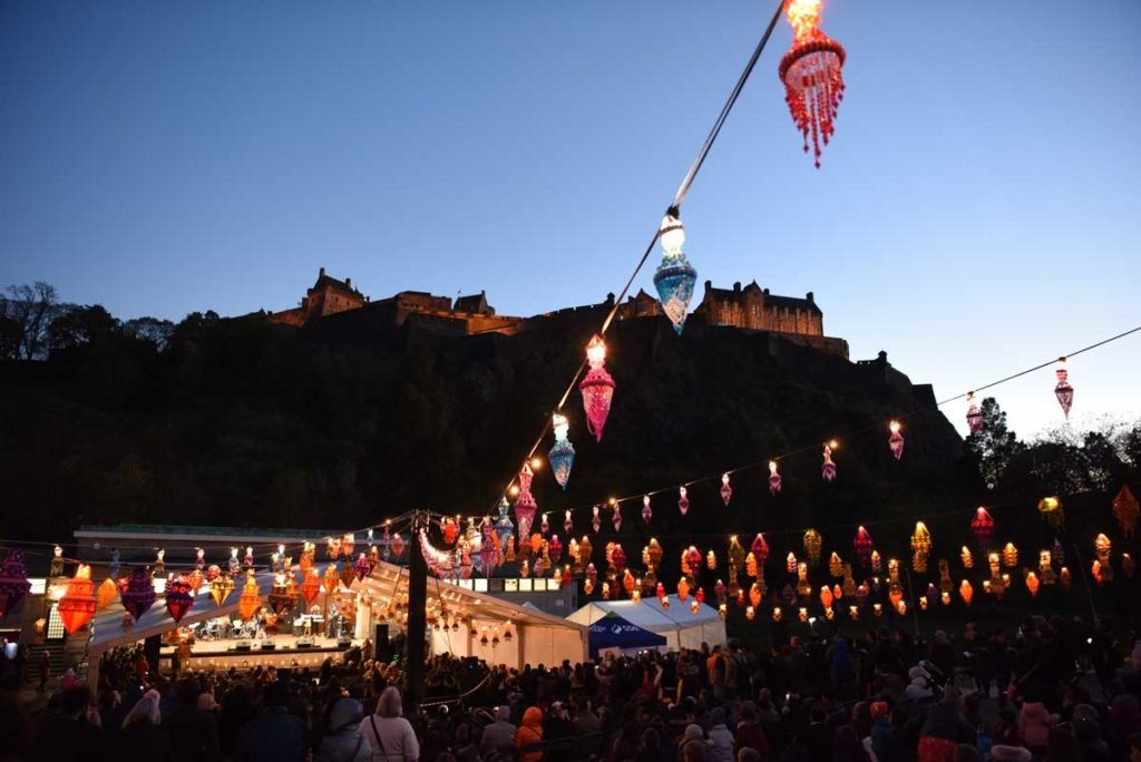 Colourful hanging lanterns leading to a bandstand with Edinburgh Castle behind