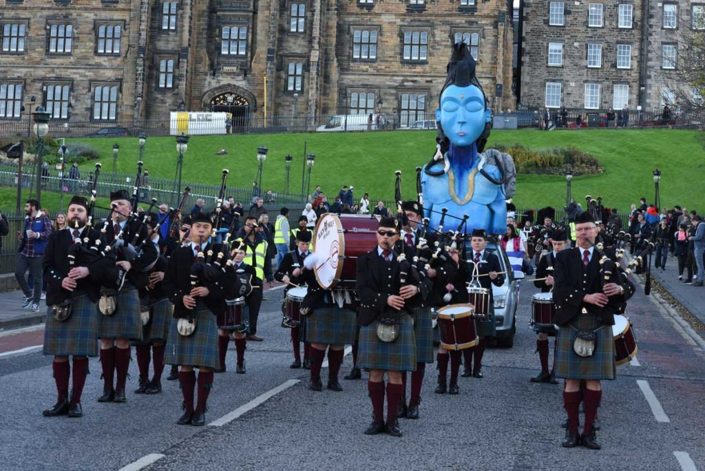 Bagpipers wearing kilts march down a road, carrying a blue Hindu effigy
