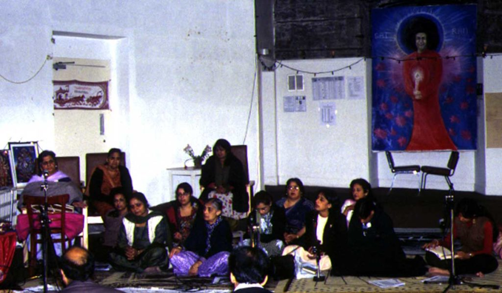 Women of colour sitting cross-legged in a community building. A large painted image is mounted on the wall behind them.
