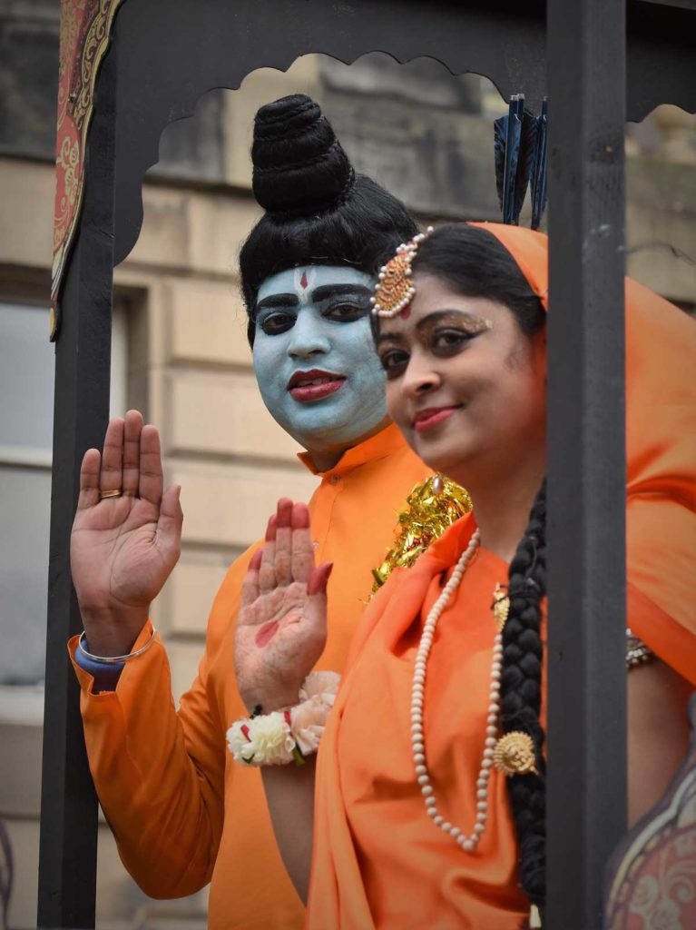 A man, wearing blue face paint, and a woman dressed in orange wave at the photographer