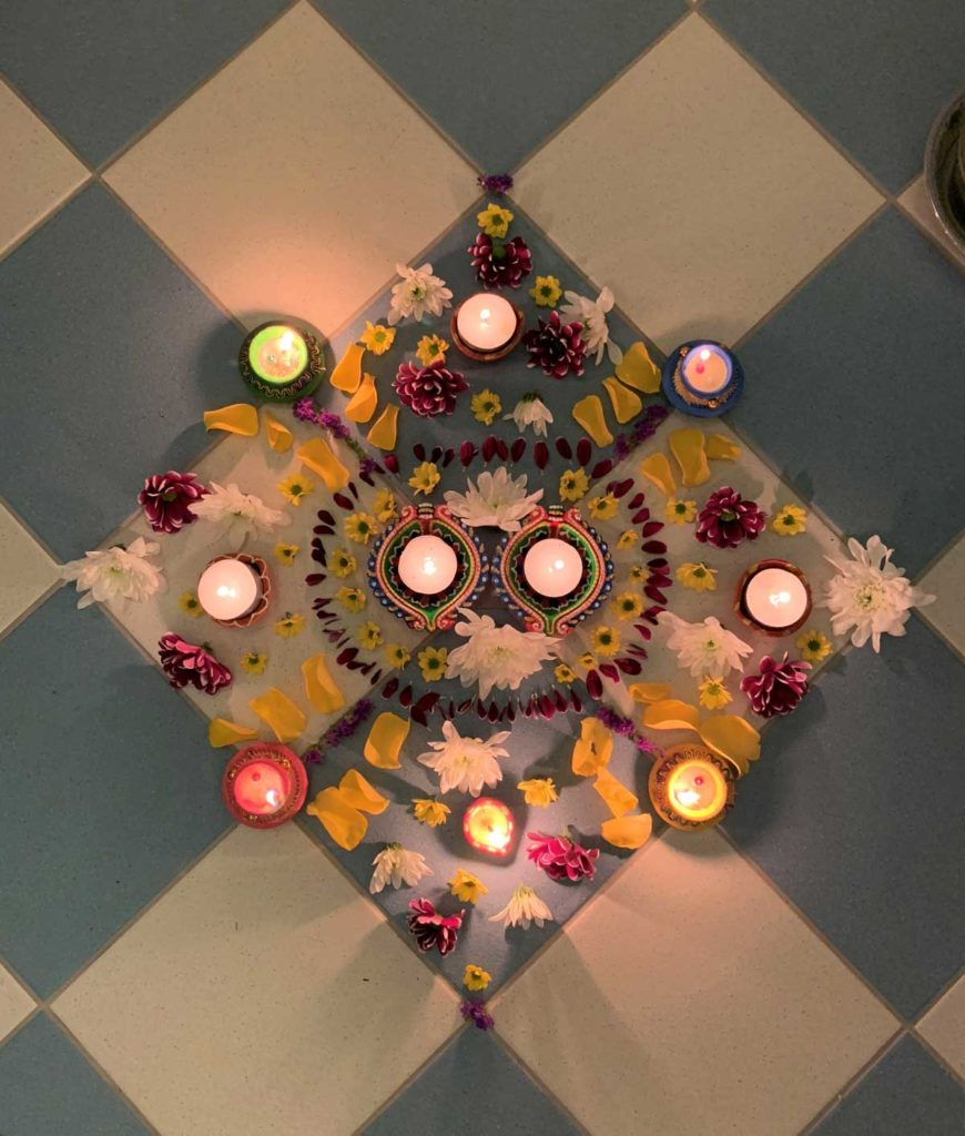 A decorative pattern on the floor, combining colourful petals and tea lights