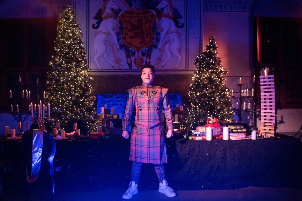 Reuben Joseph, dressed in a tartan outfit, stands in front of a long table, lit by candlelight and two heavily decorated Christmas trees