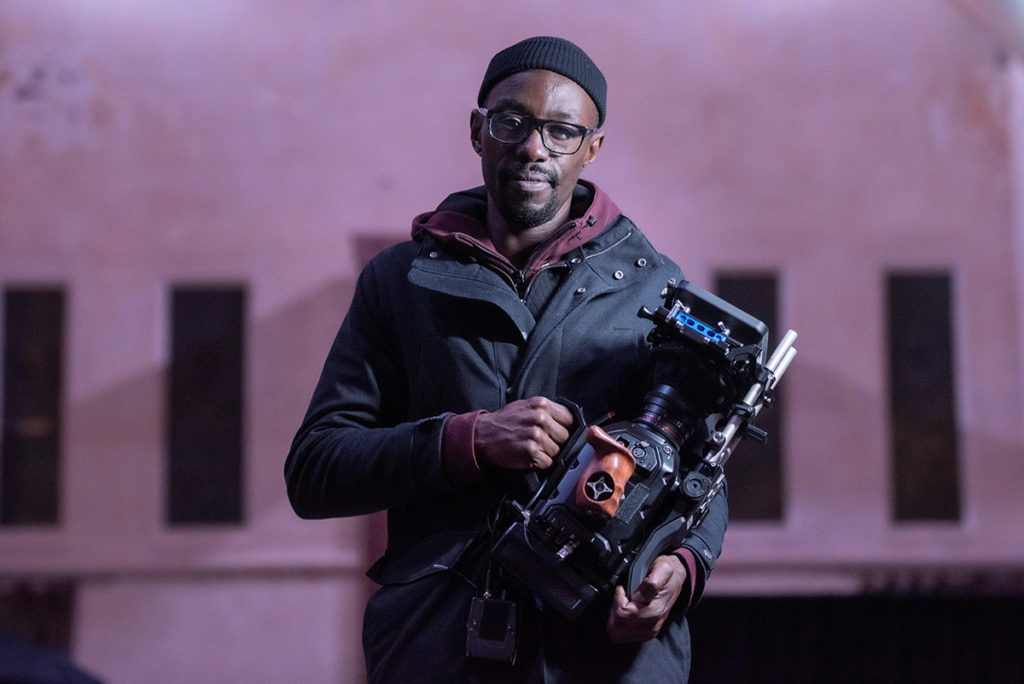 Stewart Kyasimire holds a camera in front of Stirling Castle