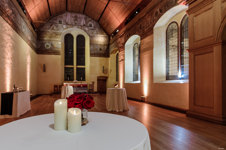 A table in a castle chapel decorated with a white tablecloth and two large candles