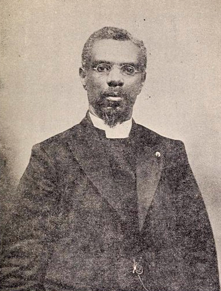 A Black man with a small beard, wearing glasses and a clerical collar looks at the camera