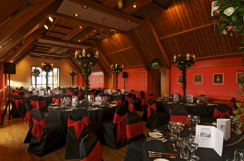 An event venue in Edinburgh Castle with a distinctive beamed ceiling and tables with a black and red theme
