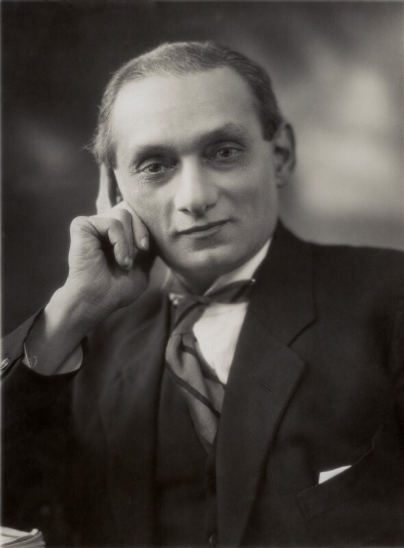 A man wearing a suit jacket leans on his hand and looks at the camera