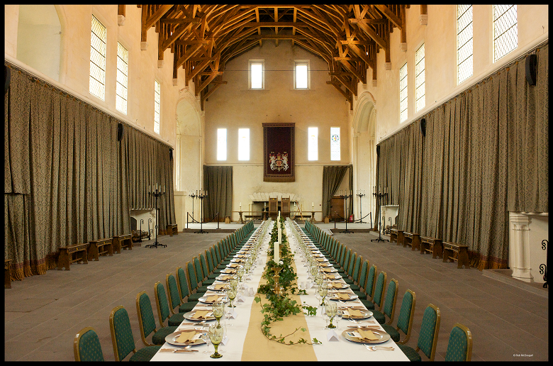 The Great Hall at Stilring Castle ready for a banquet with a long table stretching the length of the room