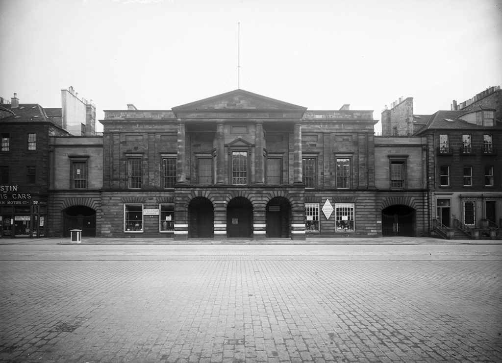 The Assembly Rooms in Edinburgh, a grand building with archways, photographed across a cobbled street