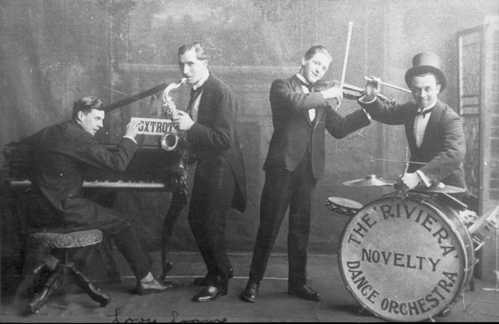 Four men in suits playing instruments - one is a drum with 'the riviera novelty dance orchestra' written on it