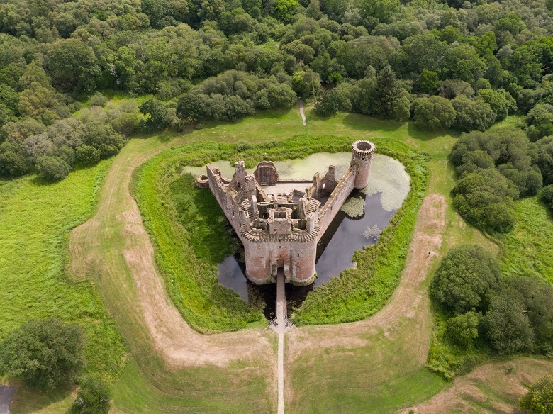 Aerial view of the ruins of a triangle-shaped castle surrounded by a moat