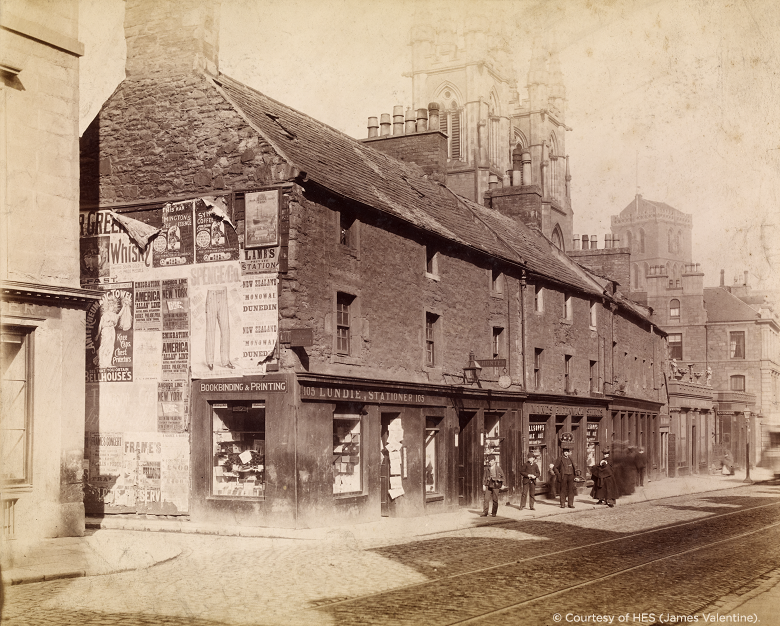 a sepia photo of a row of shops, including bill posters