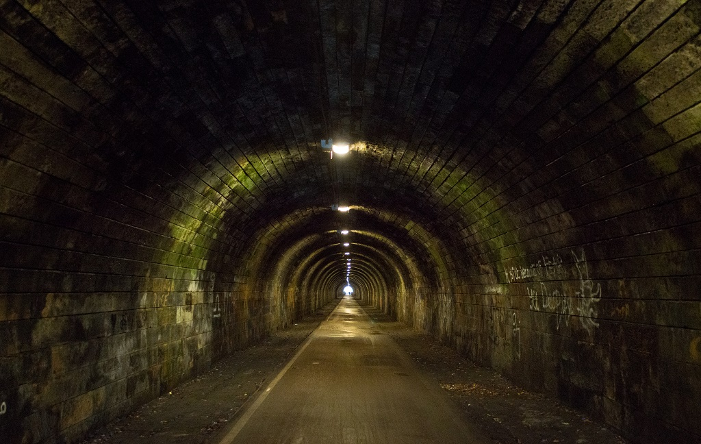 Looking down an empty former railway tunnel which has been converted into a cycle path. Lights on the roof illuminate the path at regular intervals