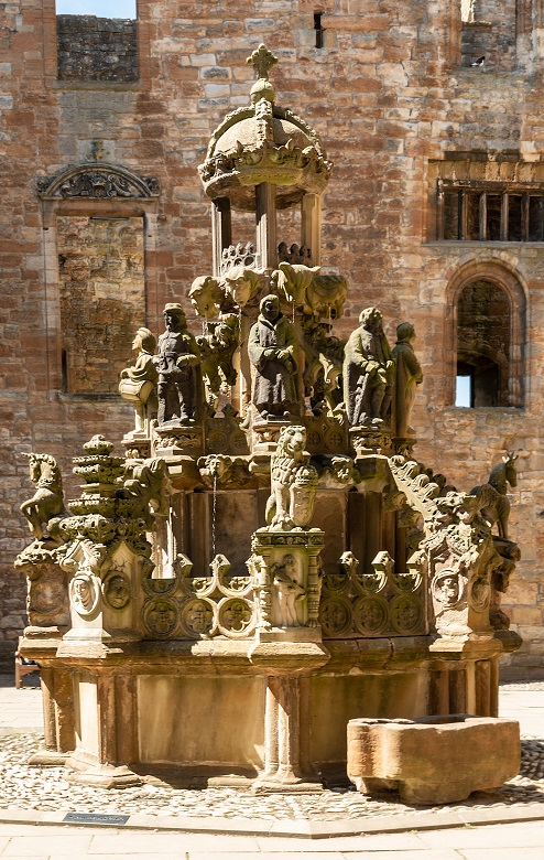 An ornately carved stone fountain in the courtyard of a palace