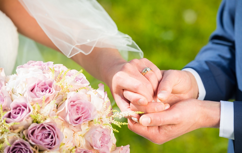 Stock image of a man in a suit placing a wedding ring on the finger of a bride in a white dress