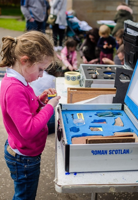 A young girl engrossed in objects in an educational box containing replica Roman objects