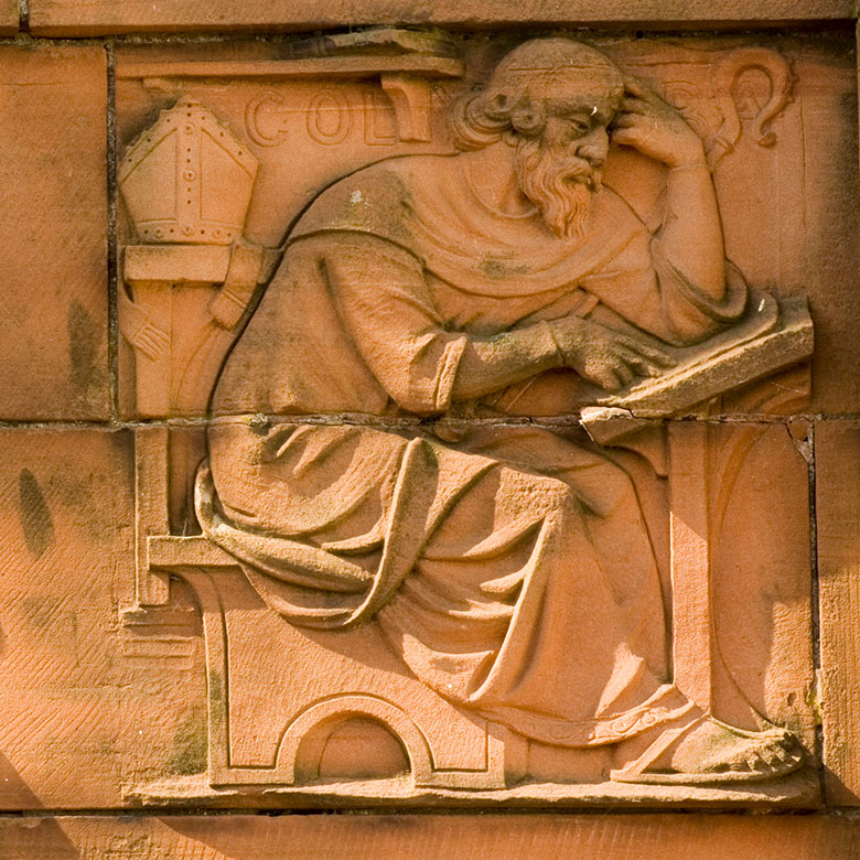 relief carving of st columba at a desk