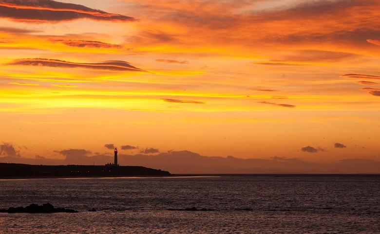 A lighthouse on a rocky promontory set against an orange sky