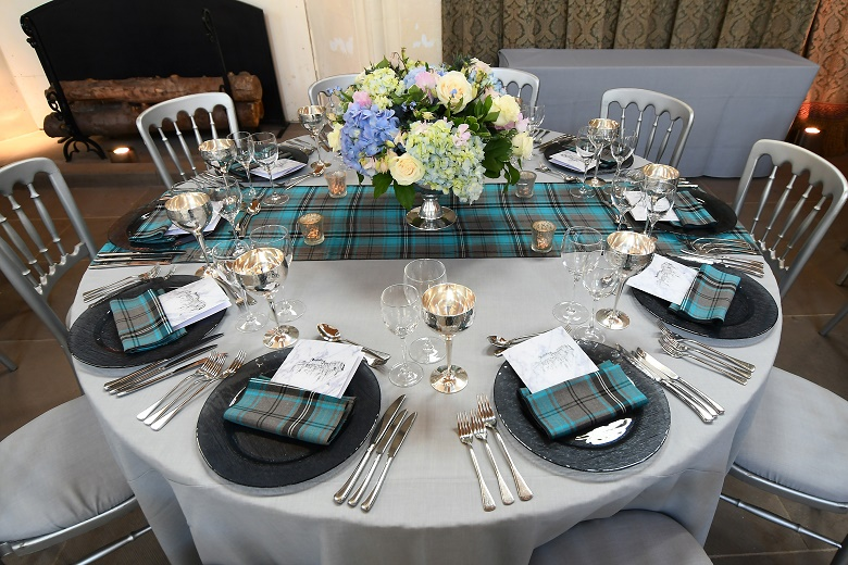 A circular table laid out for a gala dinner featuring a centrepiece of colourful flowers, tartan napkins and tablecloths, silver wine glasses and candles