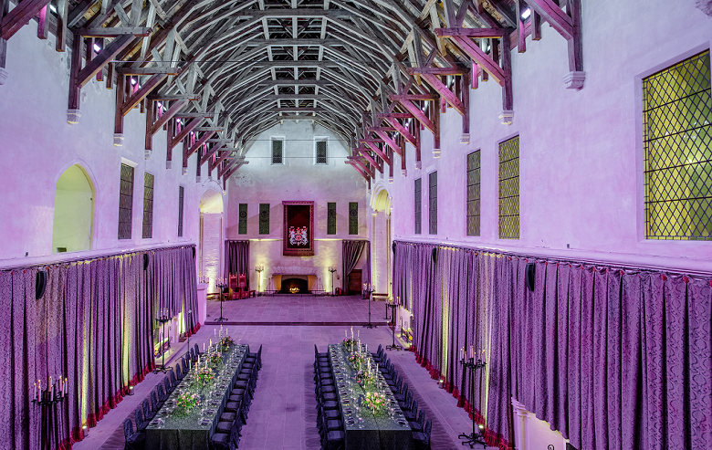 The great hall of a castle with an impressive beamed ceiling with long tables laid out ready for a banquet