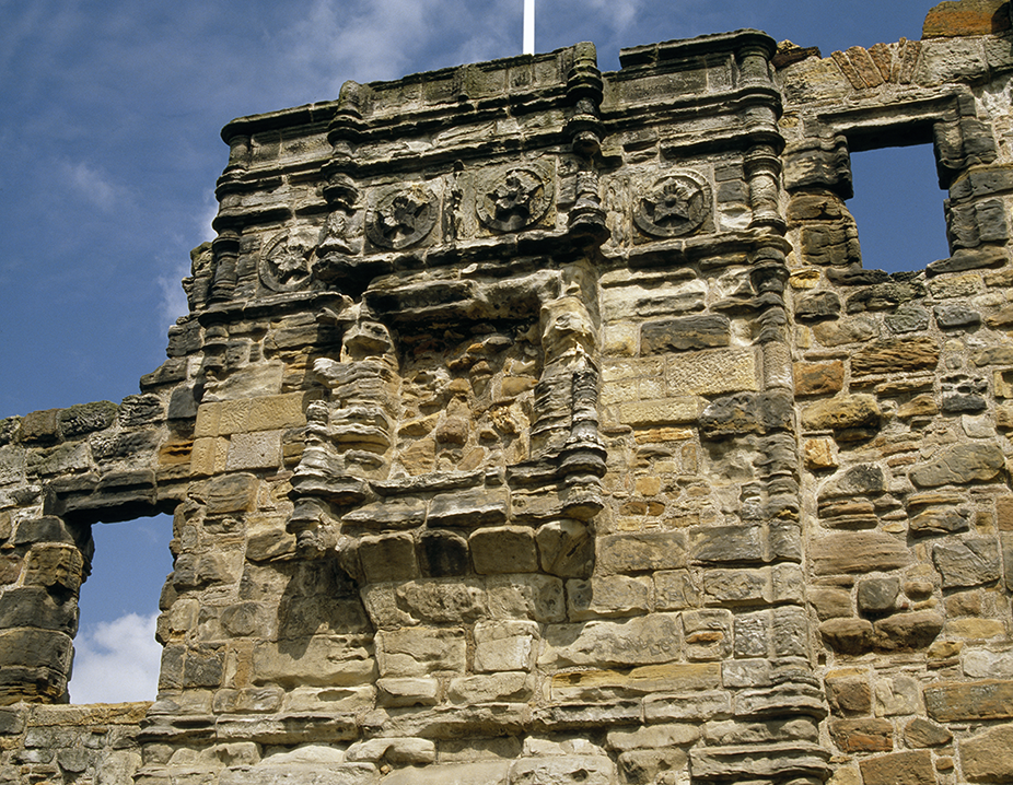 Flowers with five petals in eroded sandstone over a round arch entrance and an empty niche for a coat of arms.