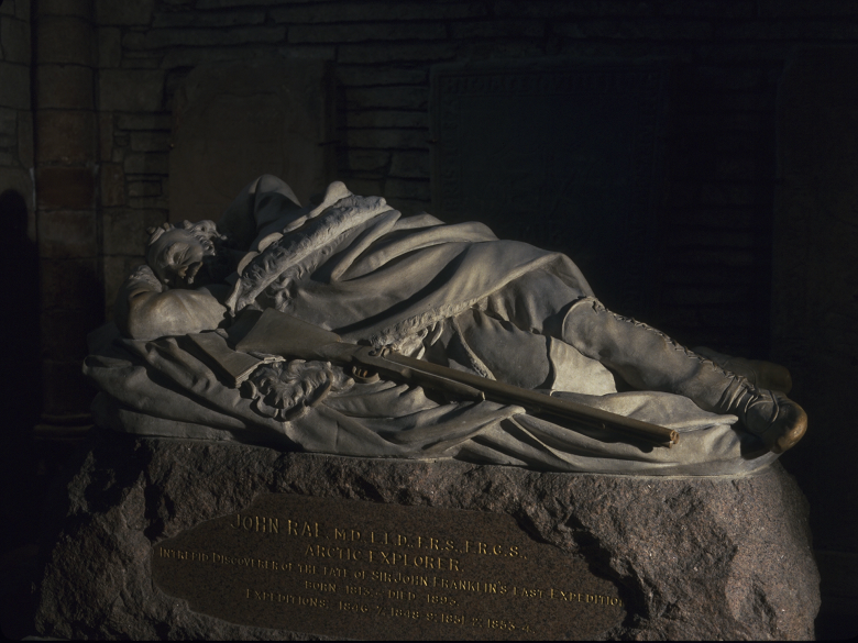 A stone memorial depicting an explorer sleeping on the open ground with a rifle beside him