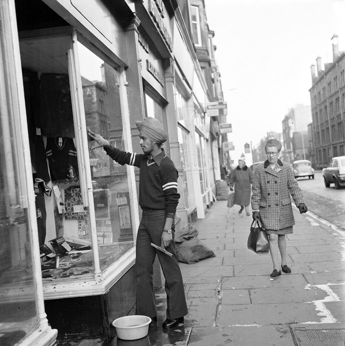 asian teenager in turban washing a shop window