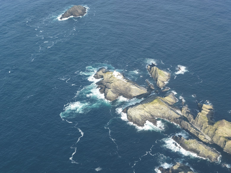 An aerial view of a group of islands with a white lighthouse building on it. A small rocky island lies just above the main group.