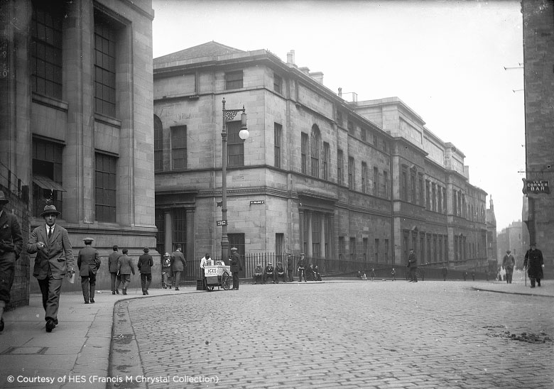 Street view of College Street Edinburgh, with pedestrians wearing period clothes.
