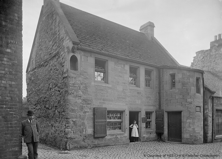 a black and white photo showing an old two storey house with a lady standing in the doorway.