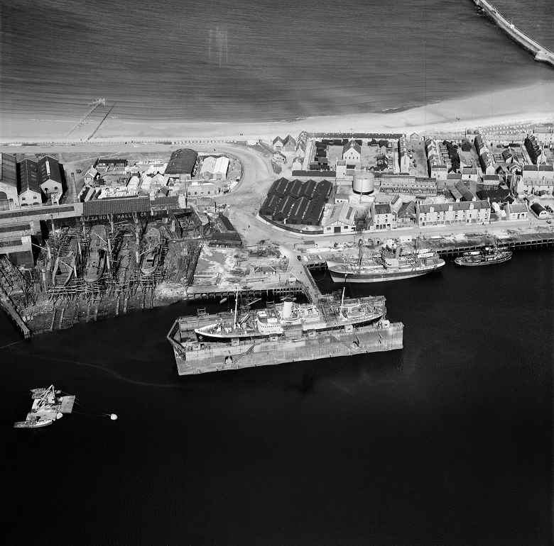 A black and white aerial photo a shipyard and docks