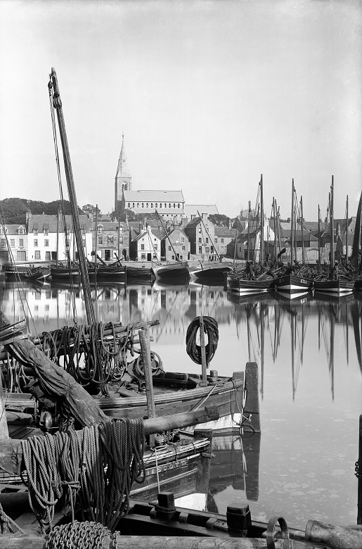 An early photograph of a small fishing port. A large church overlooks the harbour which is flanked by small cottages and busy with moored fishing vessels