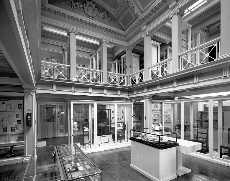 The interior of a museum with a ground floor and a mezzanine level under an ornately decorated ceiling
