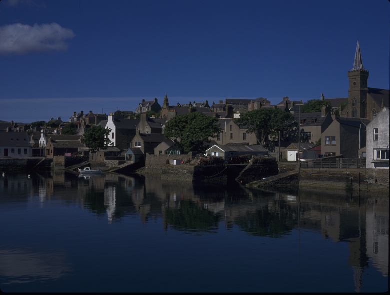 Archive photo showing still waters in the harbour of a Scottish island town. Cottages, a church and stone piers line the waterfront