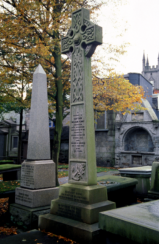 A stone celtic cross in an urban graveyard surrounded by other tombstones