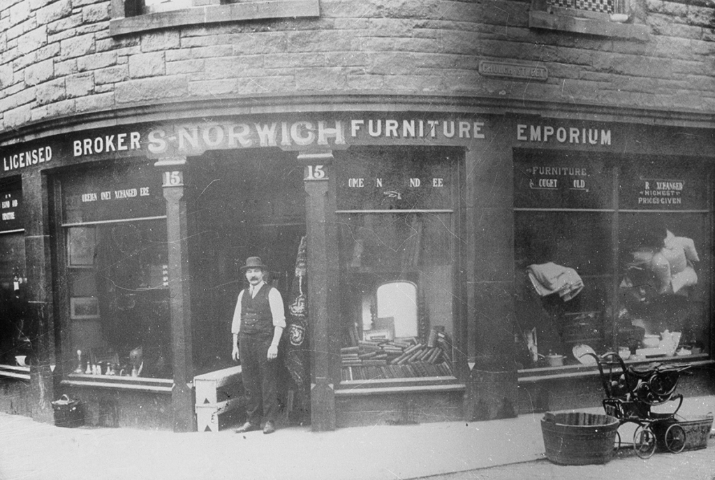 An aging photograph shows a man in a waistcoat standing in a shop door. The words above read: S Norwich Furniture