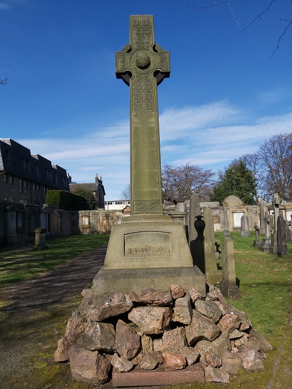 A stone cross set on a mound of rocks within a city graveyard. A lengthy inscription runs down the centre of the cross and there is an illustration of an Arctic exploration scene at the base