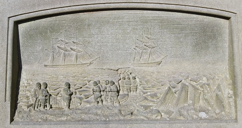 A stone carving showing around a dozen men wearing clothing designed for Arctic exploration standing on a frozen sea in front of two ships. Some of the men appear to be pulling a sledge and others appear to be digging a grave,