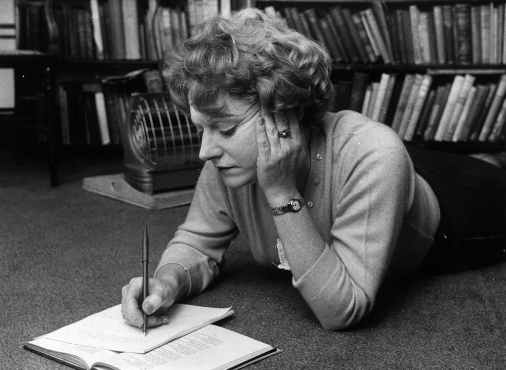 Muriel Spark lying on her front, writing with a pen and writing her head in her hand