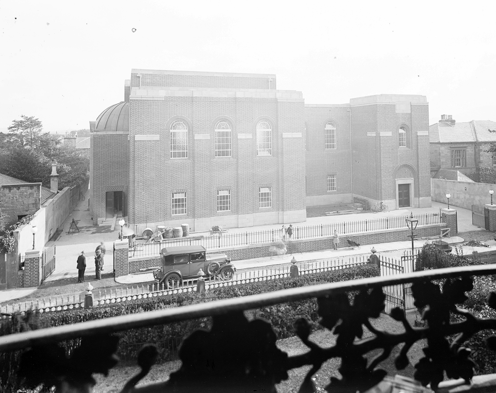 Photograph taken from a balcony opposite of a brick synagogue and an old fashioned car driving past