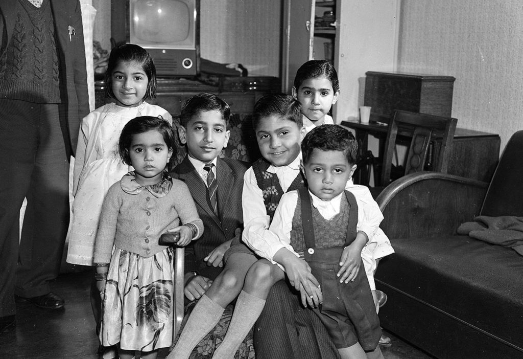 A Pakistani family of six children and a father in a tenement living room