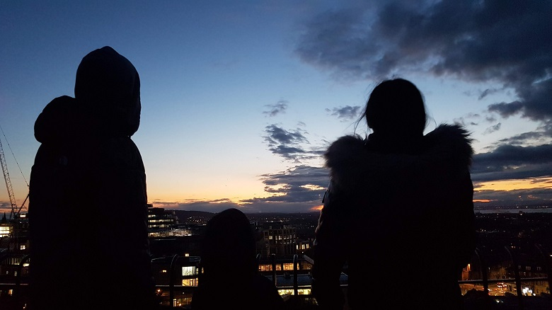 Silhouette of a family staring out to the horizon of Edinburgh at twilight