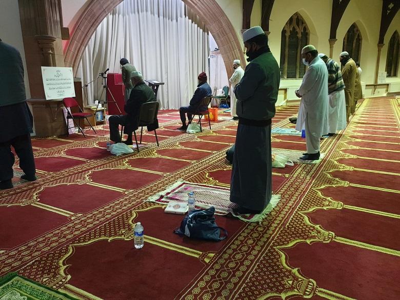 Men in traditional Muslim dress attend prayer in a socially distanced manner