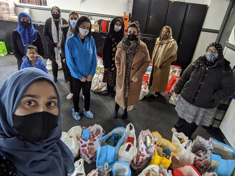 A group of Muslim women wearing covid face masks stand around bags of groceries at a food bank