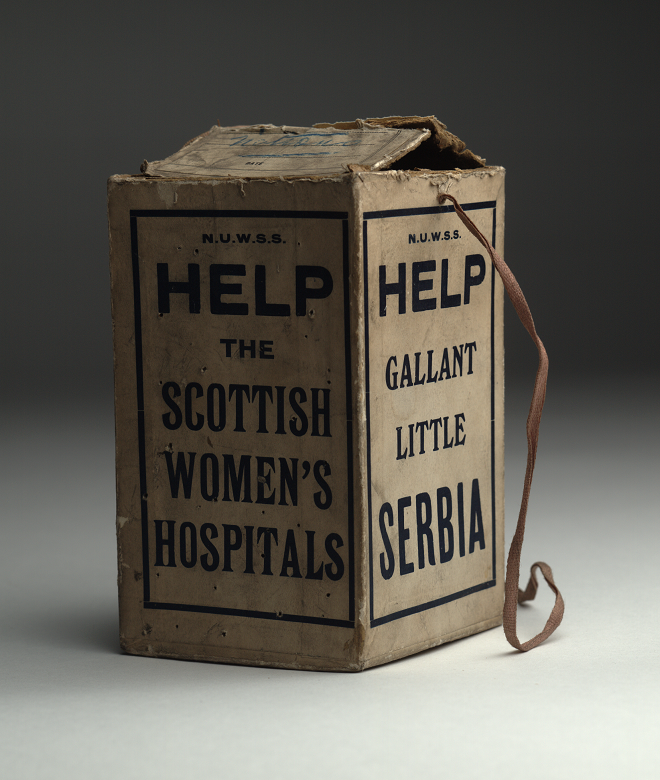 """A cardboard box on a string, used for collecting money. Slogans on the side of the box read """"Help the Scottish Women's Hospitals"""" and """"Help Gallant Little Serbia"""""""